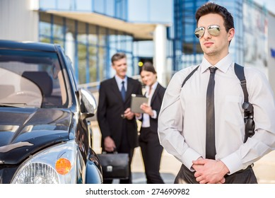 Two  successful confident businesspeople in suits   at a meeting standing near car.