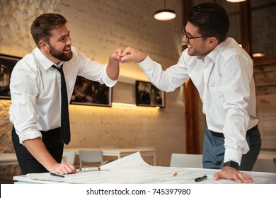 Two successful confident smart businessmen working on a business plan while standing over desk with graph and fist bumping indoors