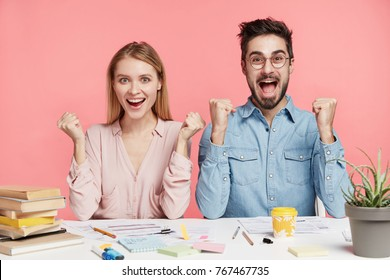 Two successful female and male students rejoice to finish working at project, raise and clench fists, have happy expressions, glad to reach goals. Partners work on common report, have good results