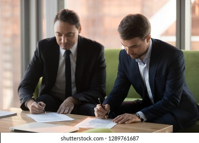 Two successful middle aged businessmen in suits signing contracts for services at meeting, satisfied male business partners put signature on legal papers making deal agreement writing on documents