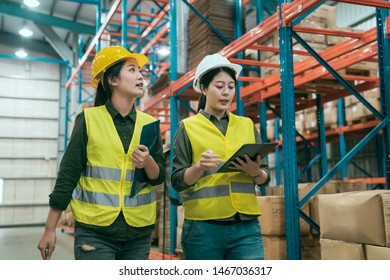 Two successful smiling businesswoman walking through big warehouse with helmets on their heads. woman manager holding digital tablet and colleague beside carry documents with clipboards in stockroom.