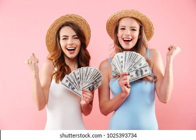 Two successful women on summer holiday in swimsuits clenching fists while holding fans of money cash in hands isolated over pink background