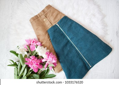 Two suede skirts on white fur. Bouquet of peonies. Fashionable concept