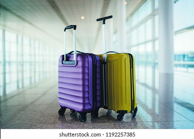 Two suitcases in the airport departure lounge, holidays concept, empty area for copy space or text message, yellow and purple suitcases in empty hall