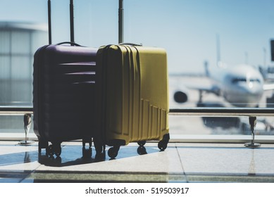 Two suitcases in the airport departure lounge, airplane in the blurred background, summer vacation concept, traveler suitcases in airport terminal waiting area, empty hall interior with large windows