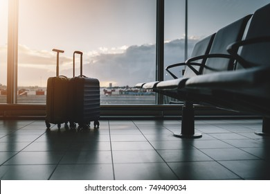 Two suitcases in empty airport waiting hall, vacation concept, flare light effects