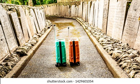 Two suitcases on a sidewalk between tombstones in the Abbey Graveyard in the village of Athlone, the trip of no return, wonderful sunny day in the county of Westmeath, Ireland