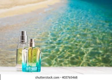 Two summer perfumes on white wooden table against defocused coastline.