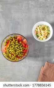 Two summer salads of fresh vegetables in plates on a gray background - Shutterstock ID 1778836145