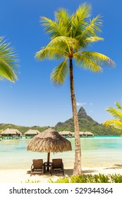 Two sun lounger chairs under a thatched parasol on a sand beach with a view on the lagoon and Mount Otemanu on the tropical island of Bora Bora, near Tahiti, in French Polynesia.