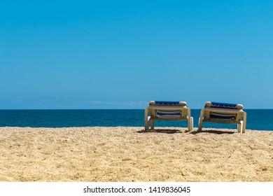 Two sun loungers on sandy beach in sunny weather. Beach loungers on Mediterranean sea coast under blue sky.