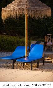 Deux chaises longues et un parasol en paille près de la piscine