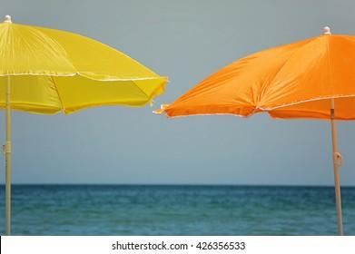 two sun shield umbrellas against sea scape background