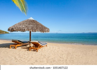 Two sunbeds under a straw umbrella on the tropical beach of Nosy Be, Madagascar