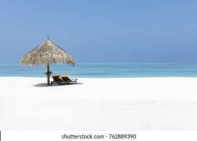 Two sunbeds under a thatched umbrella on white sand on a tropical beach paradise, with space for text