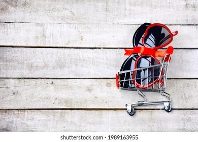 dos gafas de sol en el tranvía de supermercado, concepto de promociones, venta, descuentos, mesa de madera blanca