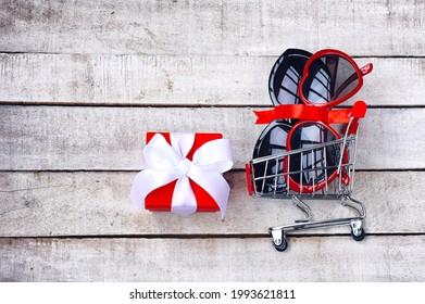 dos gafas de sol en un tranvía de supermercado, caja de regalo, concepto de promociones, venta, descuentos, mesa de madera blanca,