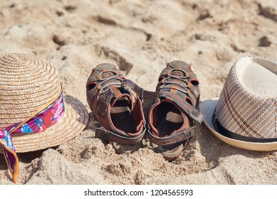 Two sunhats and kid's sandals are laying at the sand. Close up.
