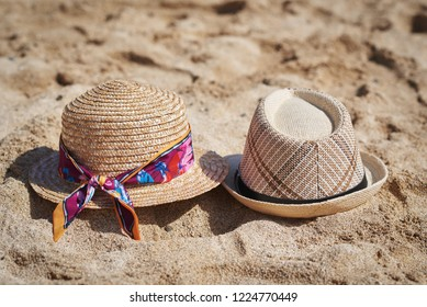 Two sunhats are laying on the sand at the beach.