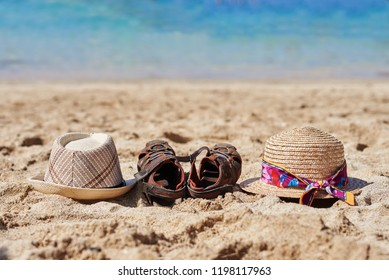 Two sunhats and a pair of kid's sandals between are laying on the sand near the ocean.