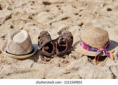 Two sunhats and a pair of kid's shoes are laying on the sand.
