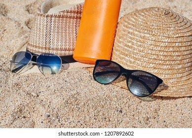 Two sunhats, sunglasses and sunprotection cream are laying on the sand.