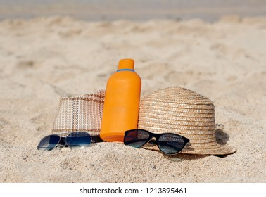 Two sunhats, sunglasses and sunscreen crean are laying on the sand near the sea, illustrating healthy way of life.