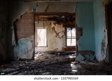 Two sunlit windows viewed through two rooms of a dilapidated abandoned farm house
