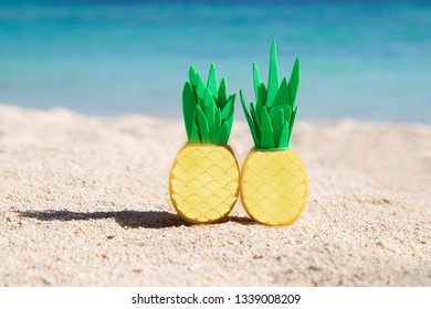 Two sunny easter eggs with pineapple leaves on the sandy beach near the ocean