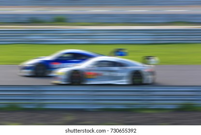 Two super car race on the race track with motion blur.