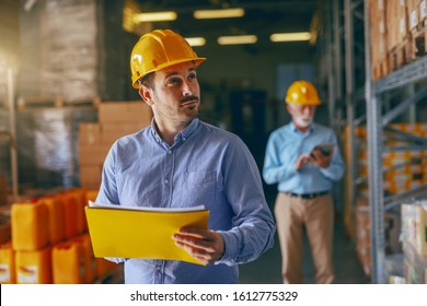 Two supervisors going around warehouse and analyzing sales in warehouse. In foreground younger one holding folder with data and looking at cargo. In background older one using tablet.