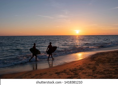 Two surfer dudes walking with their surf boards along the Englewood beach coastline in Englewood, Florida at sunset.
