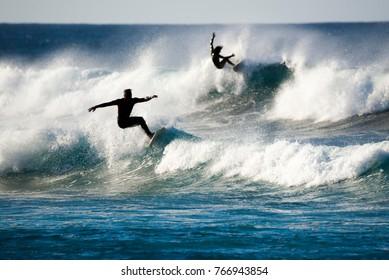 dos surfistas en acción sobre las olas