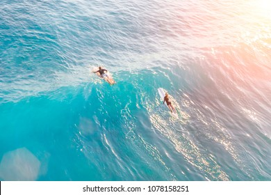 Two surfers in a calm ocean on a sunny day, top view