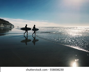 Two surfers on the beach in San Diego