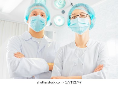 Two surgeons doctors in a mask and a cap in a hospital