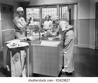 Two surgeons and a nurse in the scrub room preparing for an operation