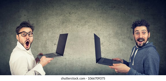 Two surprised funny men with new laptops standing against gray wall background