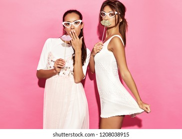 Two surprised funny women in paper glasses and big lips on stick. Smart and Beauty concept. Joyful young models ready for party. Girls isolated on pink background. Positive female