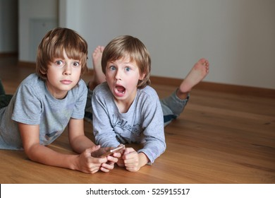Two surprised kids lying on wooden floor and using mobile phone