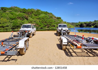Two SUV cars carrying boats on beach. Shot in Sodwana Bay Nature Reserve, KwaZulu-Natal province, Southern Mozambique area, South Africa.