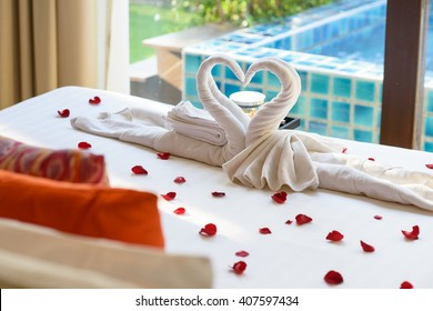 Two swans and heart made from towels on honeymoon bed