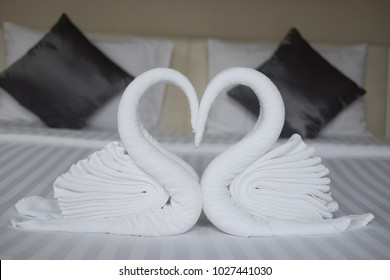 Two swans made of towels forming heart shape decorated for wedding preparation decoration