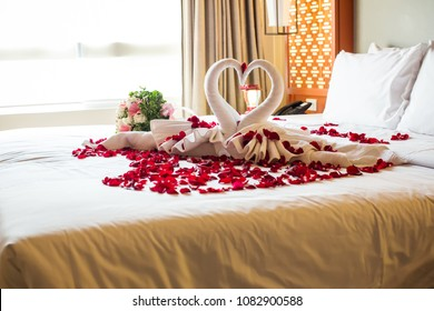 two swans made from towels are kissing on honeymoon white bed. creamy pillow and heart form, valentine signature made from red rose flower on bed decoration in bedroom.Valentine background.honey moon