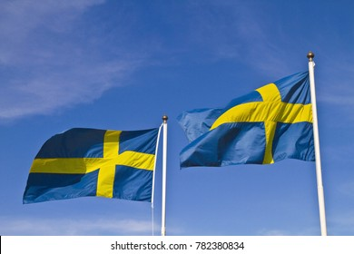 Two Swedish flags against blue sky