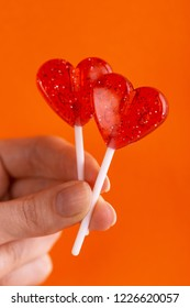 Two sweet bright red lollipops in woman's hand on bright orange background. Copy space.