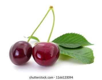 Two sweet cherries with stem and leaves on white background.