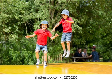 Two sweet children, boy brothers, jumping on a big trampoline, summertime