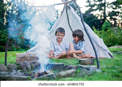Two sweet children, boy brothers, camping outside summertime on sunset, eating potatoes