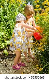 Two sweet kids watering flowers in the garden
